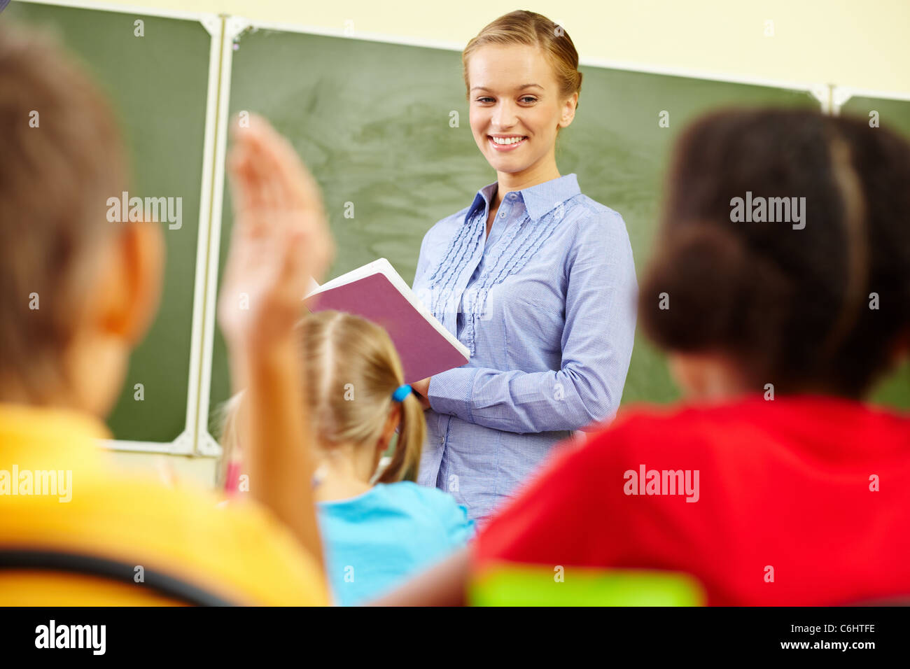 Portrait of smart teacher with exercise book looking at schoolkids in classroom - Stock Image