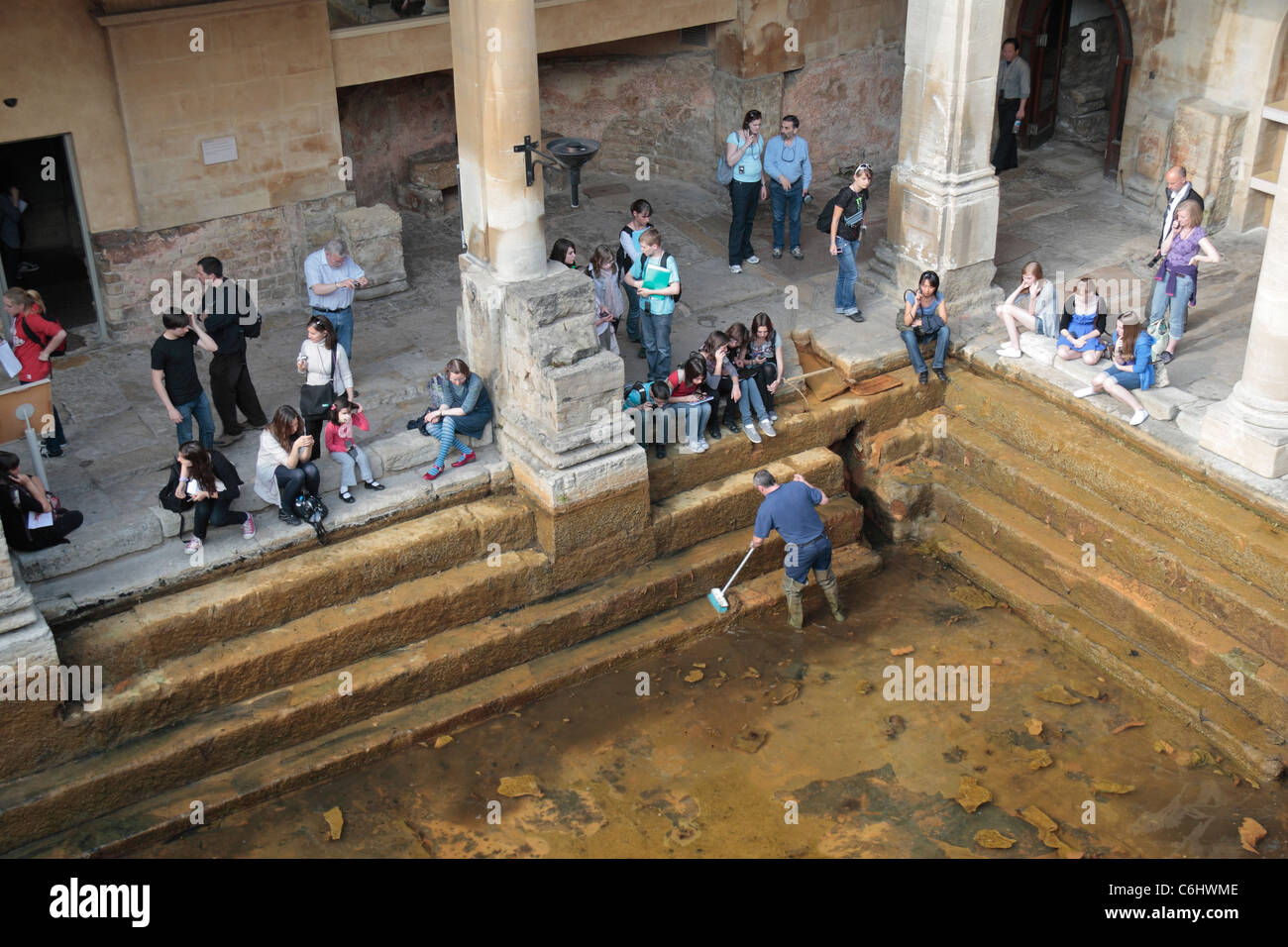 Visitors watch as the Great Bath is cleared of ochre-coloured mineral-rich sediment, The Roman Baths, Bath, Somerset, - Stock Image