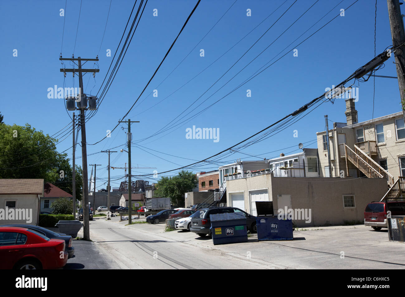 local electricity power lines and distribution in back alley of shops and houses in the french quarter winnipeg - Stock Image