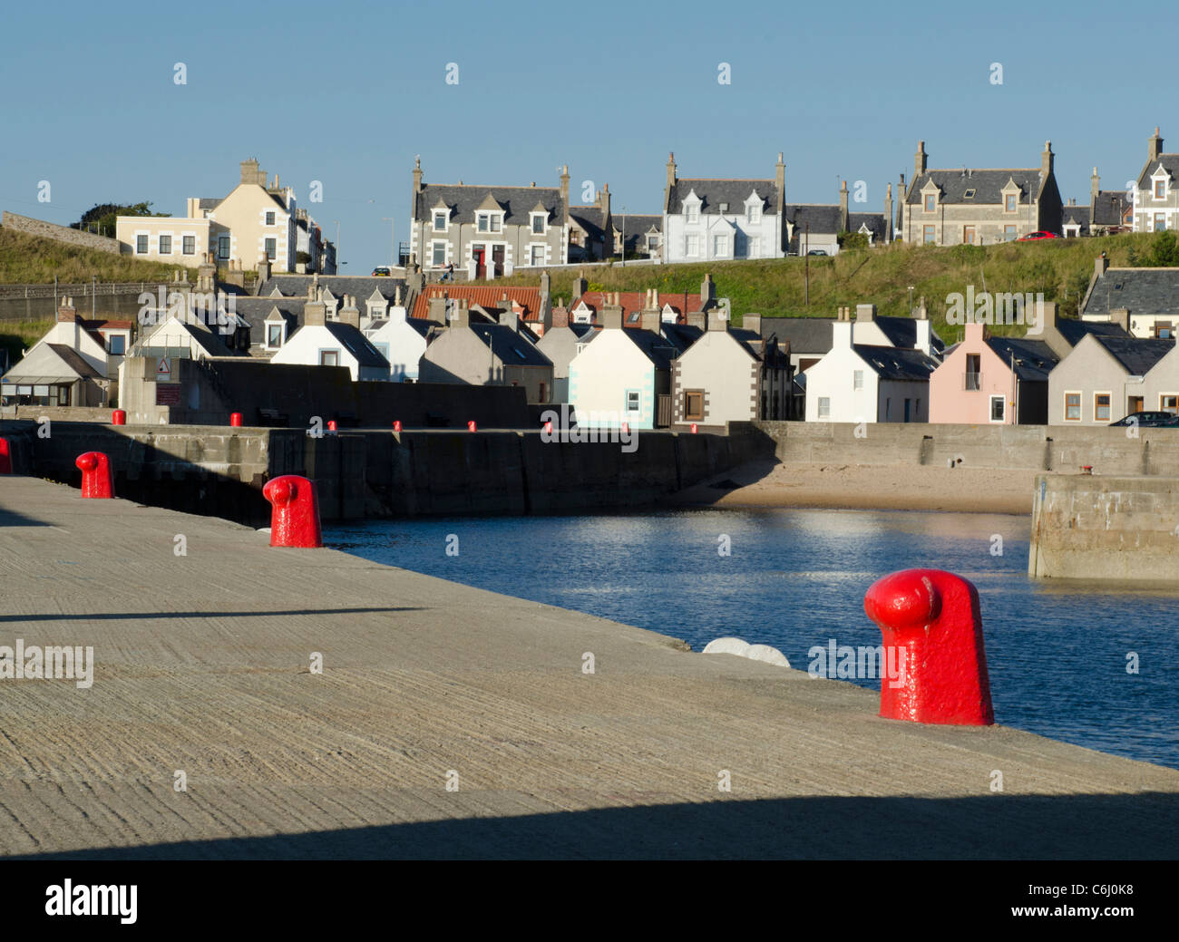 Findochty harbour with gable ends of cottages and red moorings - Moray Coast - Stock Image
