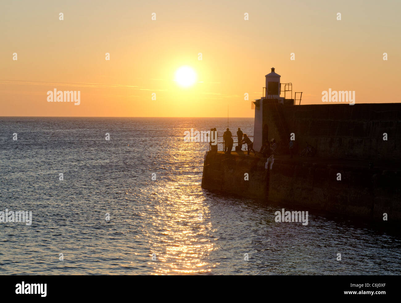 Fishermen on Pier at sunset - Whitehills Harbour - Moray Coast Aberdeenshire - Stock Image