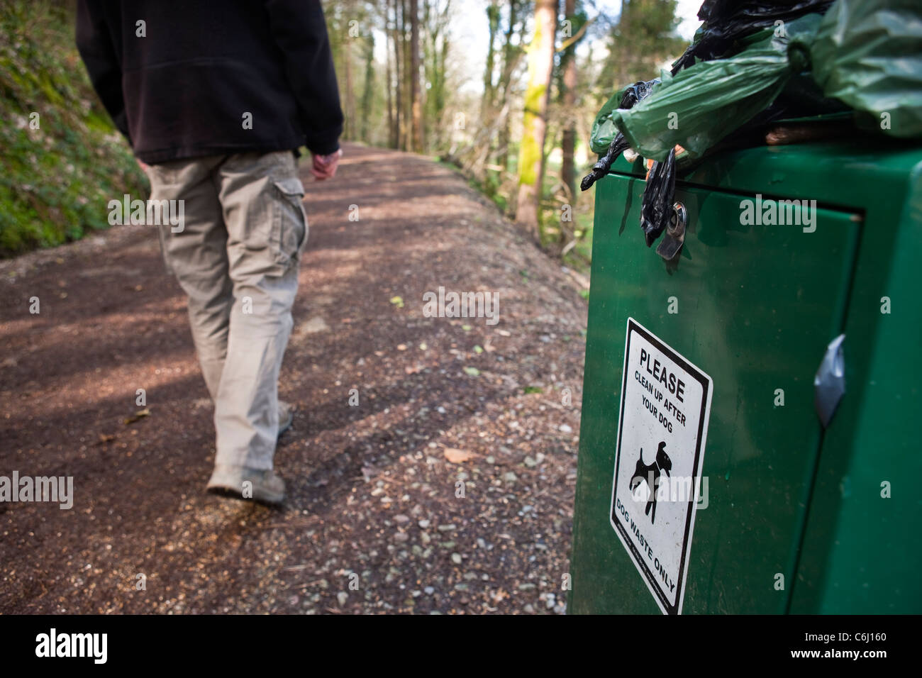 Overflowing Dog waste bin on footpath walker on path Stock Photo