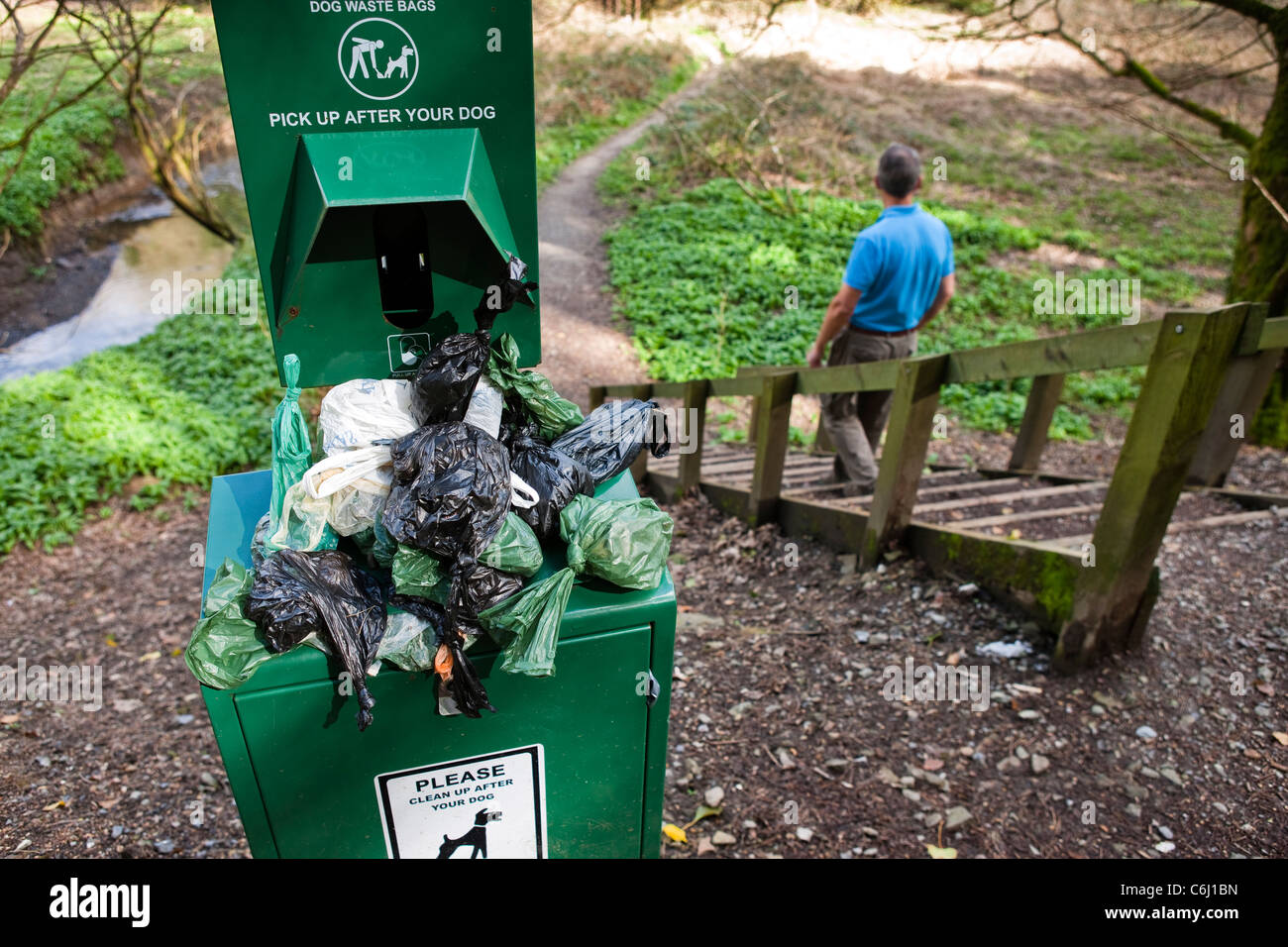 Overflowing Dog waste bin on footpath walker going down steps Stock Photo