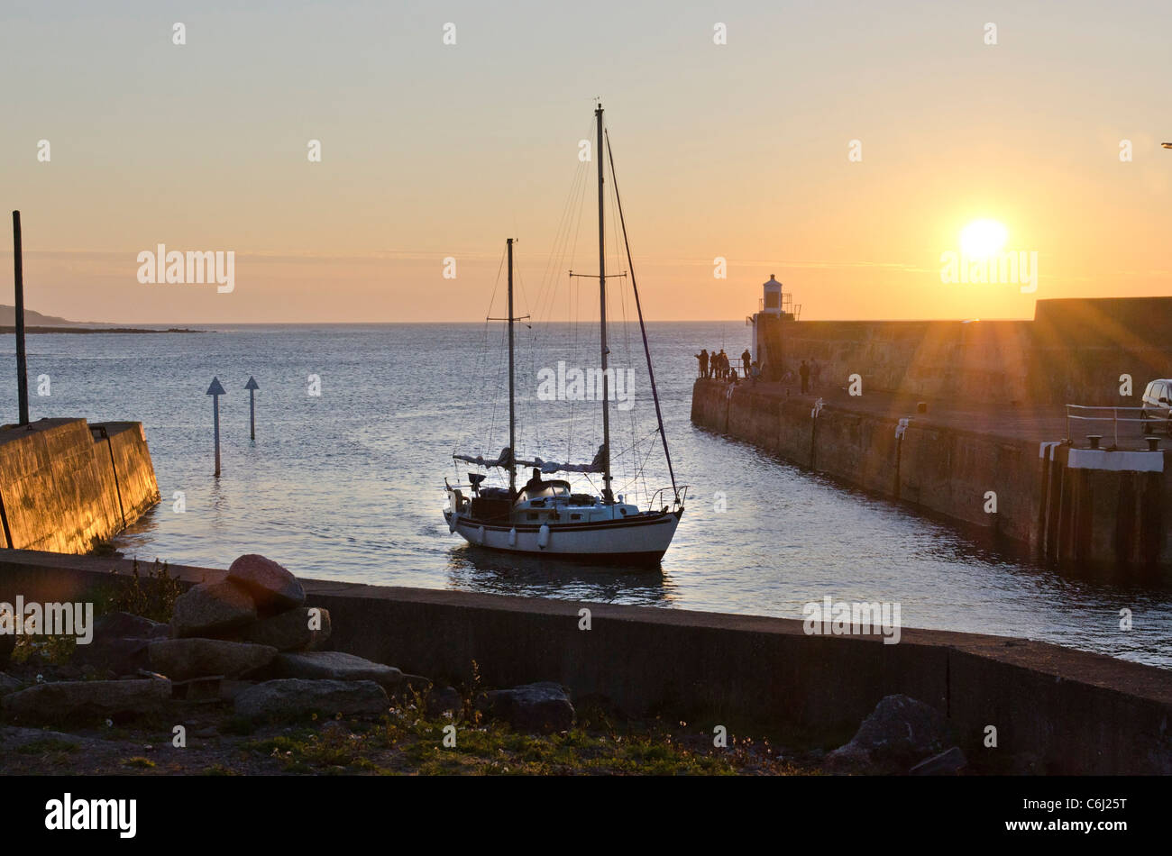 Ketch sailing boat slips into harbour at sundown - Whitehills Harbour - Moray Coast Aberdeenshire - Stock Image