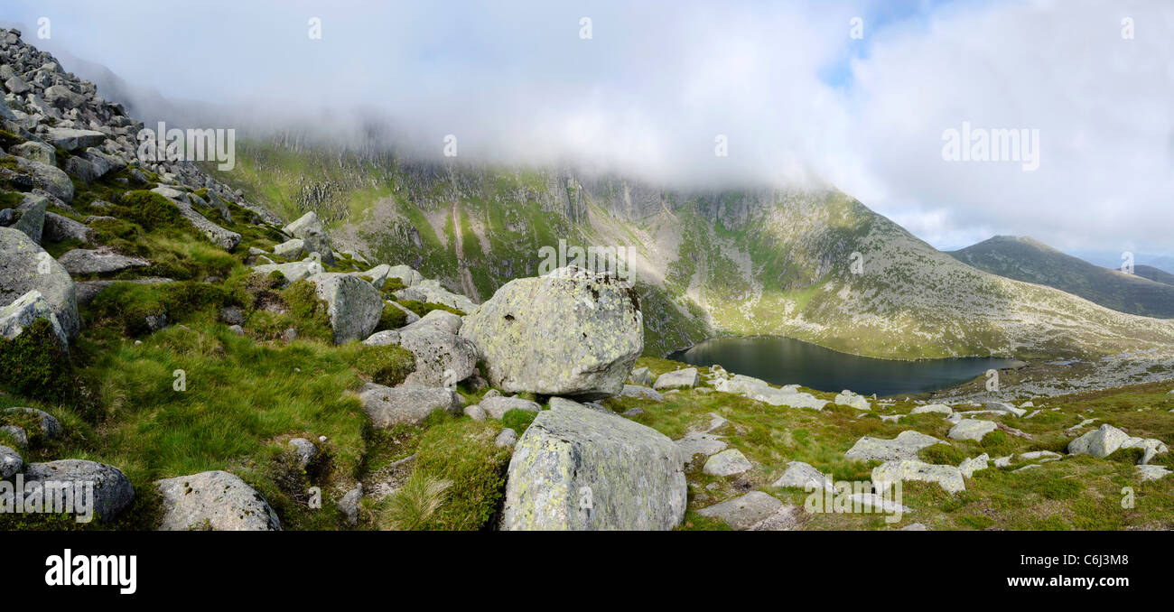 Panoramic View of Lochnagar mountain and Loch with mist rising from peaks and boulders in foreground - Stock Image