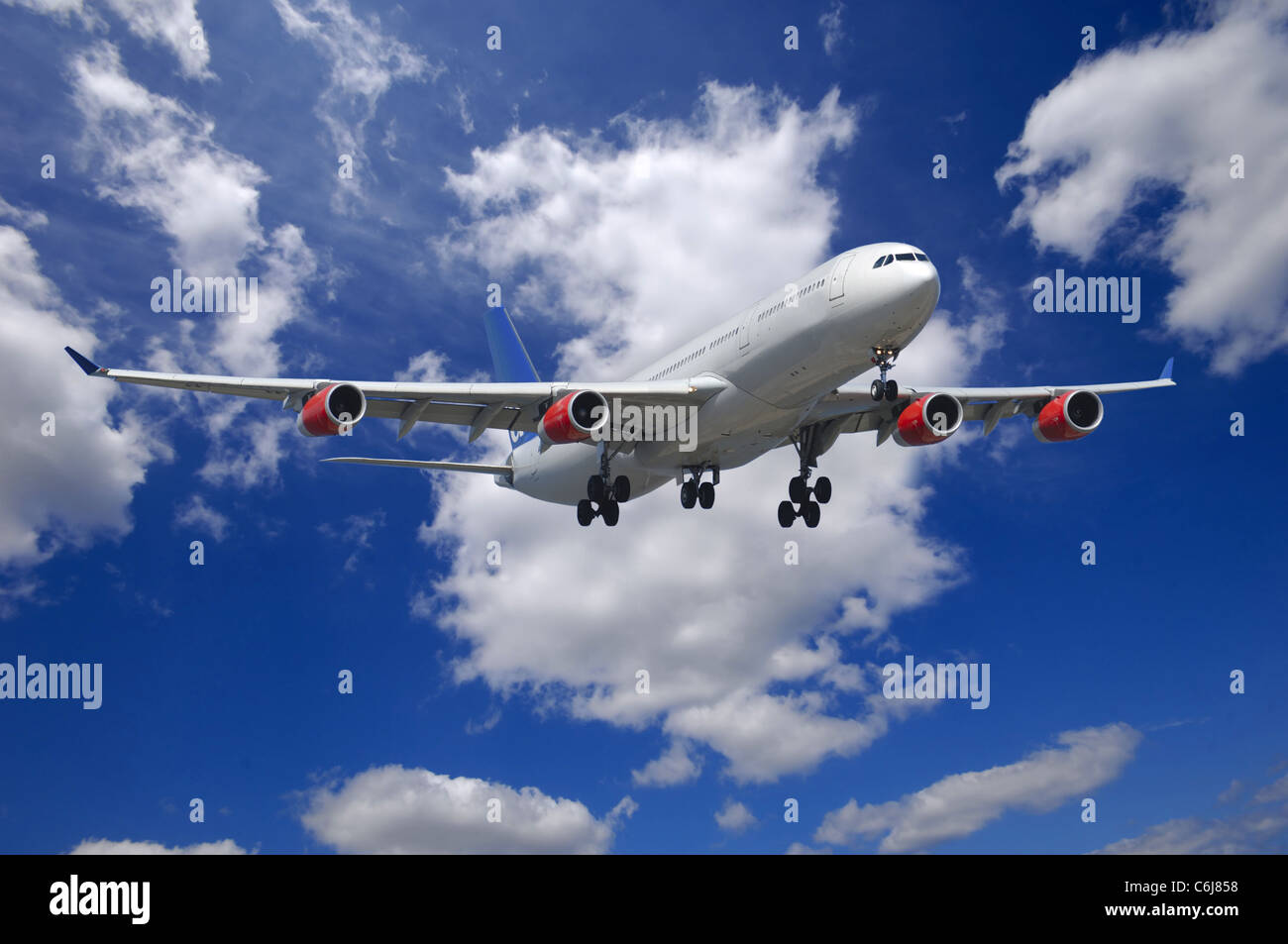 Plane going to land. Blue and cloudy sky. - Stock Image