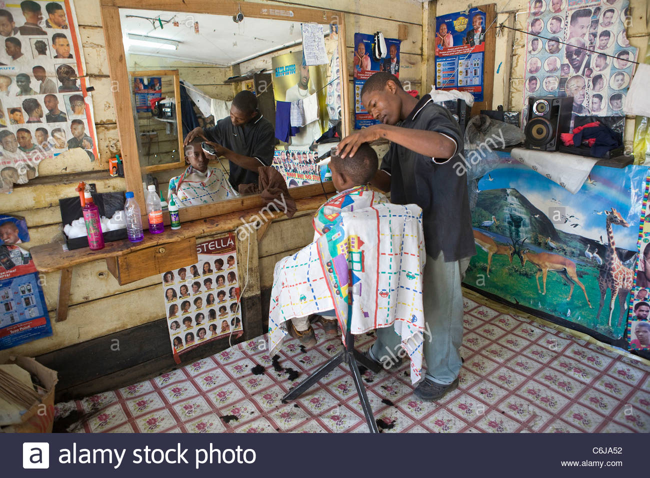 Local man having his hair trimmed with an electric trimmer at a barber shop Stock Photo