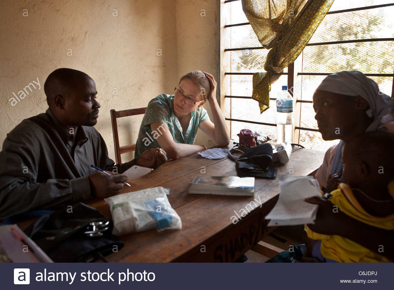 A western medical student consults with patients at a medical dispensary Stock Photo