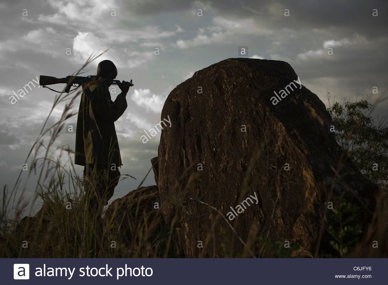 Man with a rifle over his shoulder standing under a cloudy sky - Stock Image