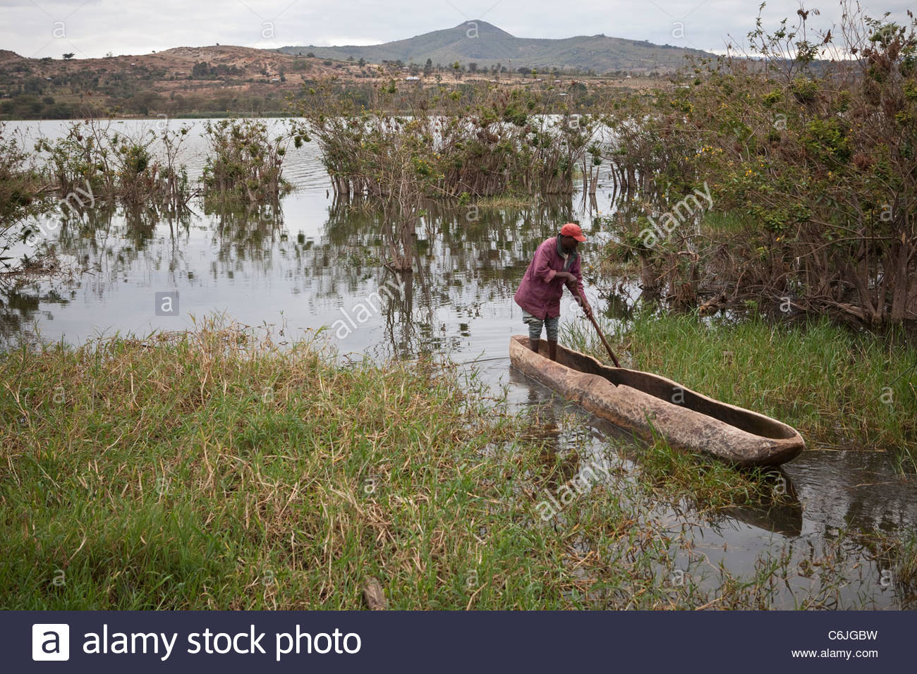 A man in a dugout canoe along the shore of Lake Babati - Stock Image