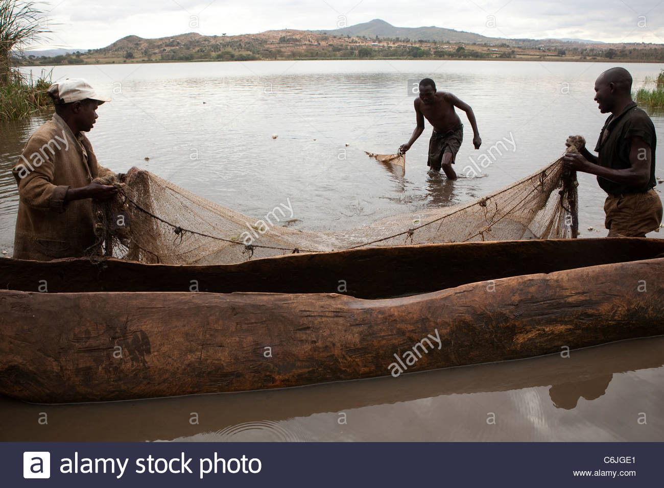 Fishermen in the water next to their dugout canoe pulling in their nets on the shore of Lake Babati - Stock Image