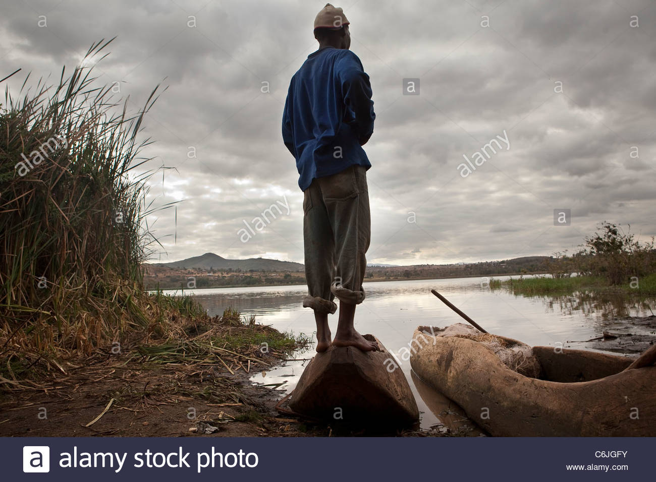 A fisherman standing on a canoe on the shore of Lake Babati with clouds overhead - Stock Image