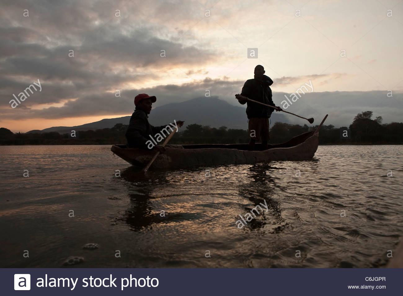 Two fishermen in a dugout canoe on Lake Babati at sunrise - Stock Image
