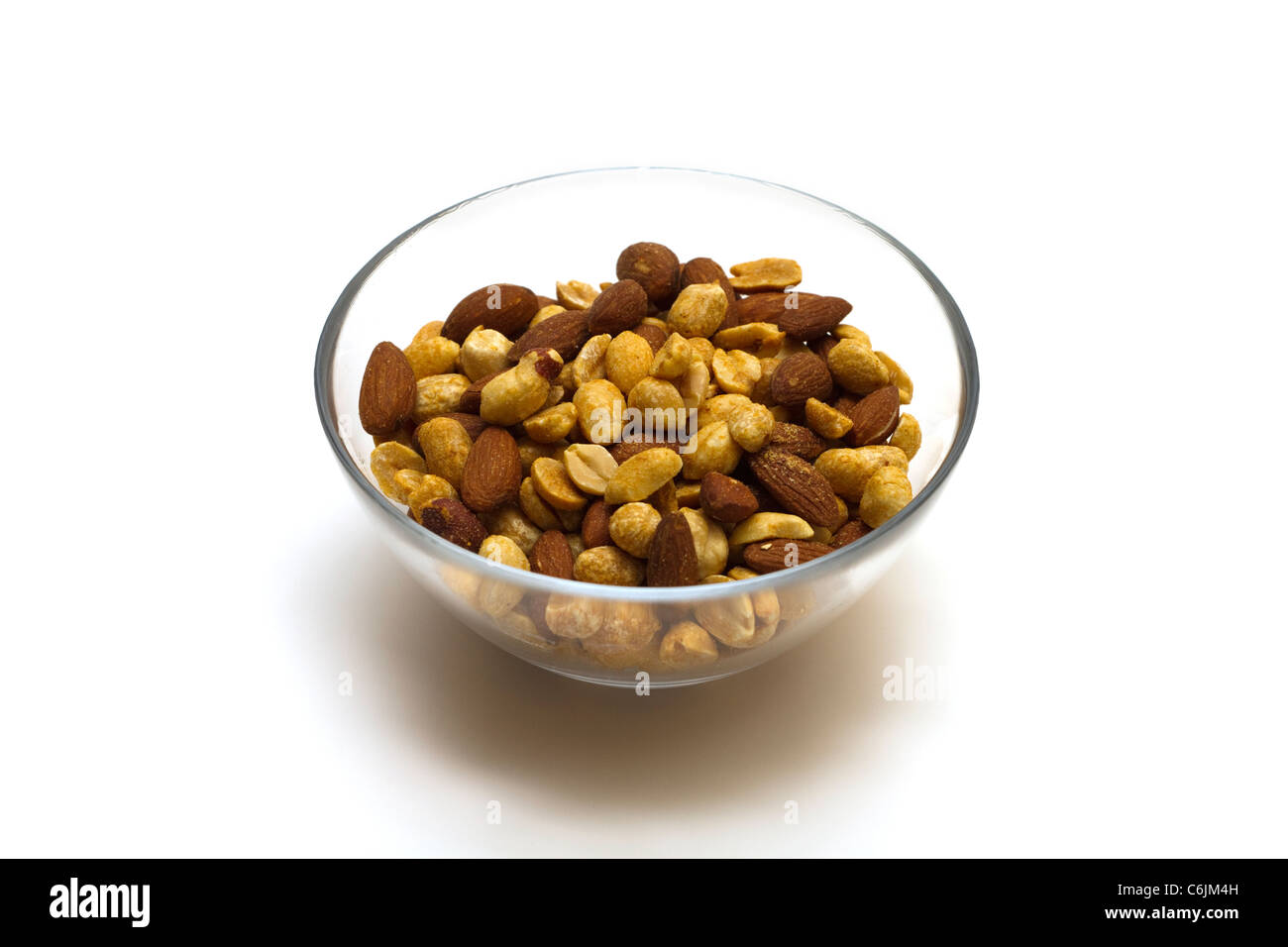 Dish of salted mixed nuts on a white background - Stock Image