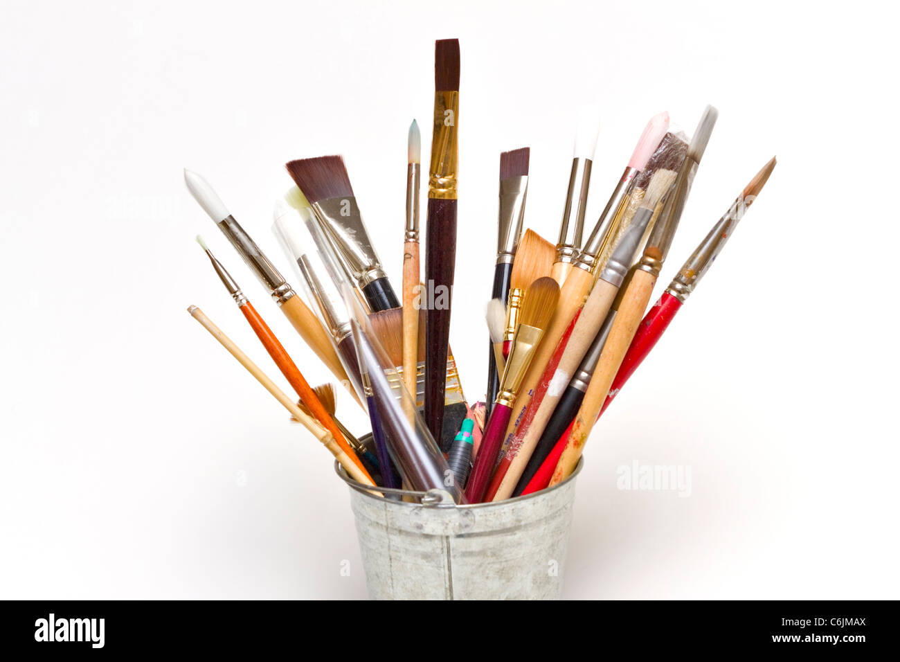 Artists paint brushes in a small bucket on a white background - Stock Image