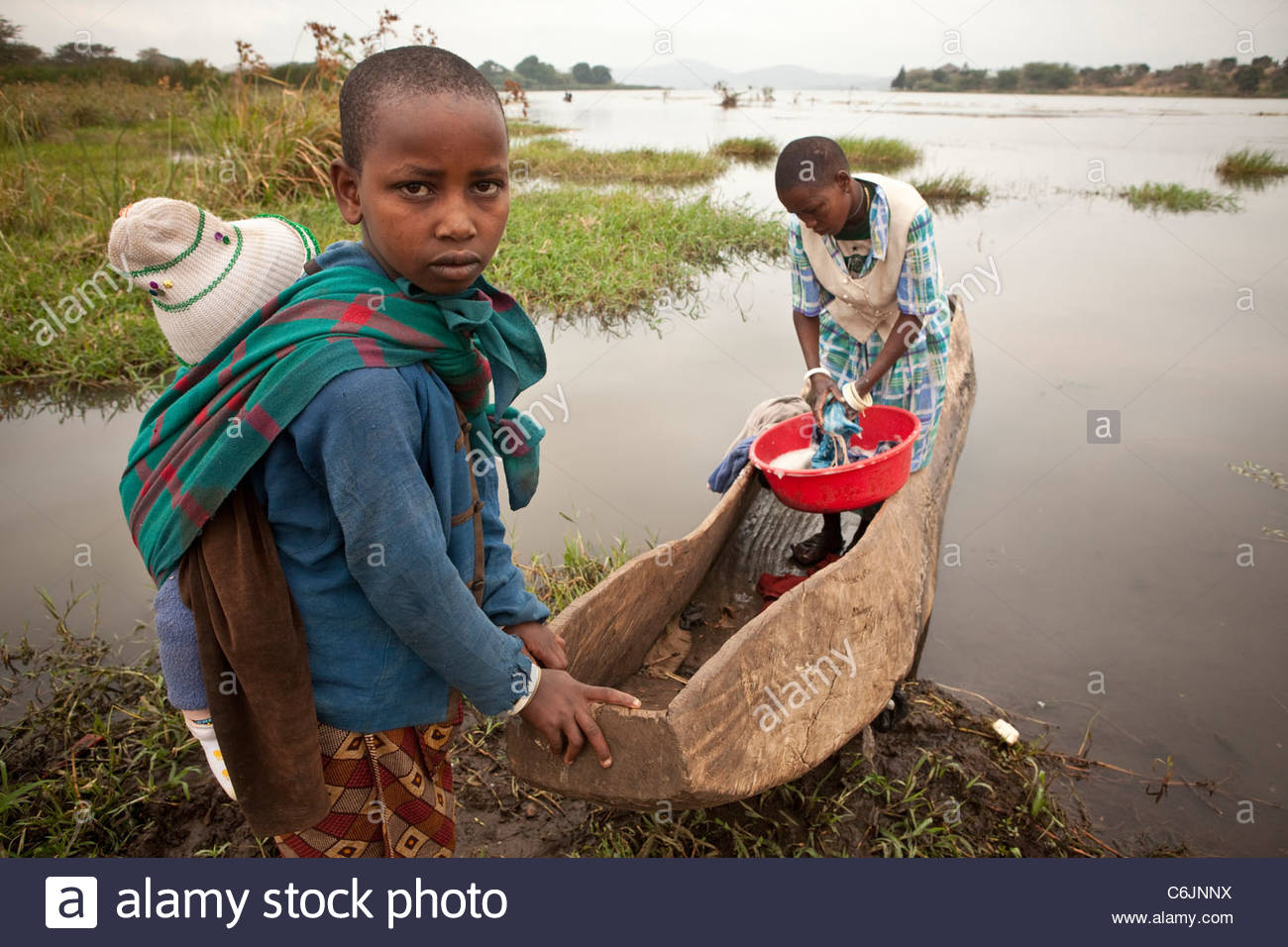 Two young girls on the shore of Lake Babati, one with a baby on her back and the other standing in a dugout canoe - Stock Image