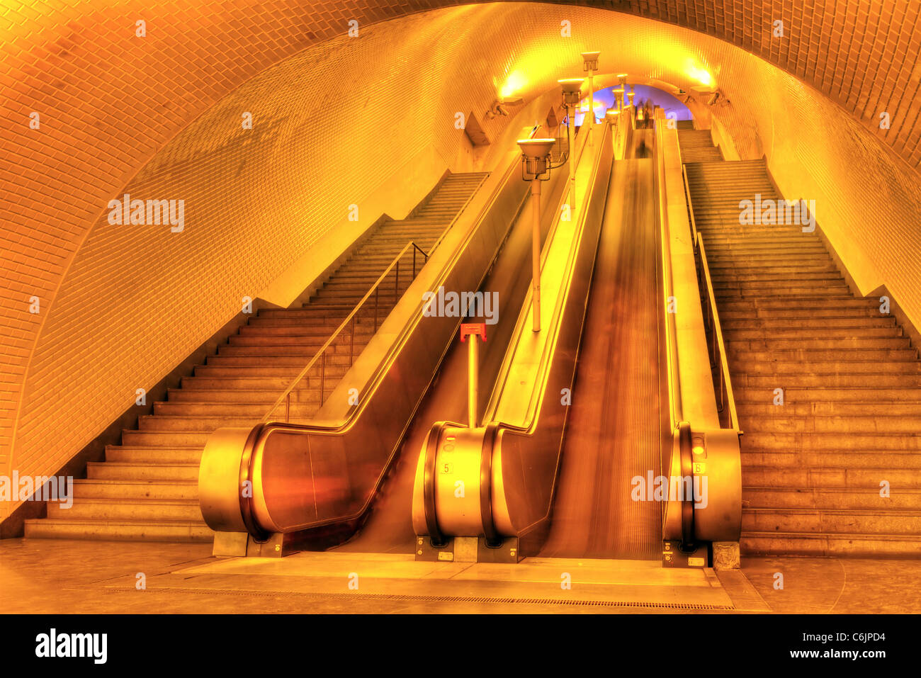 Tunnel with a long row moving stairways leading deep down to the underground subway trains of Lisboa Portugal - Stock Image