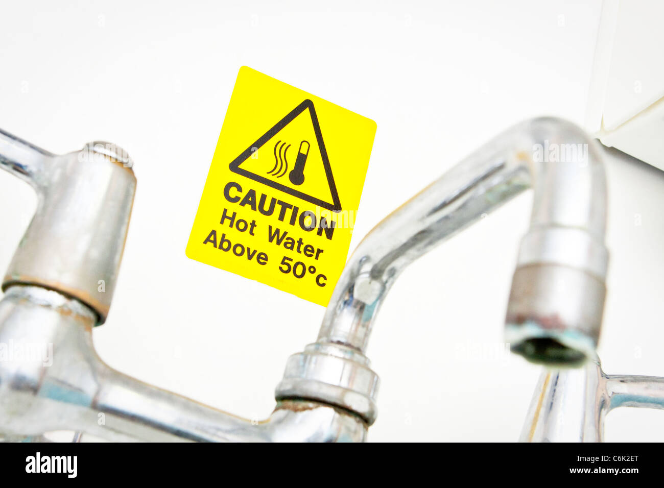A bright yellow hot water warning notice behind a chrome tap - Stock Image