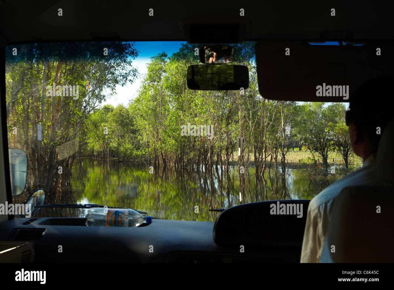 Yellow Water Cruises bus on flooded road, Yellow Water Billabong, Kakadu National Park, Northern Territory, Australia - Stock Image