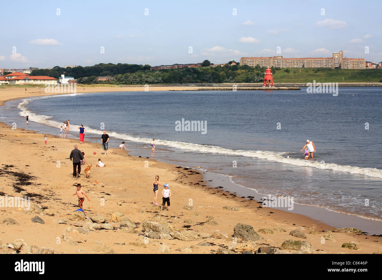Families playing at the seaside, the Herd Sand or Littlehaven beach, South Shields, North East England, UK - Stock Image
