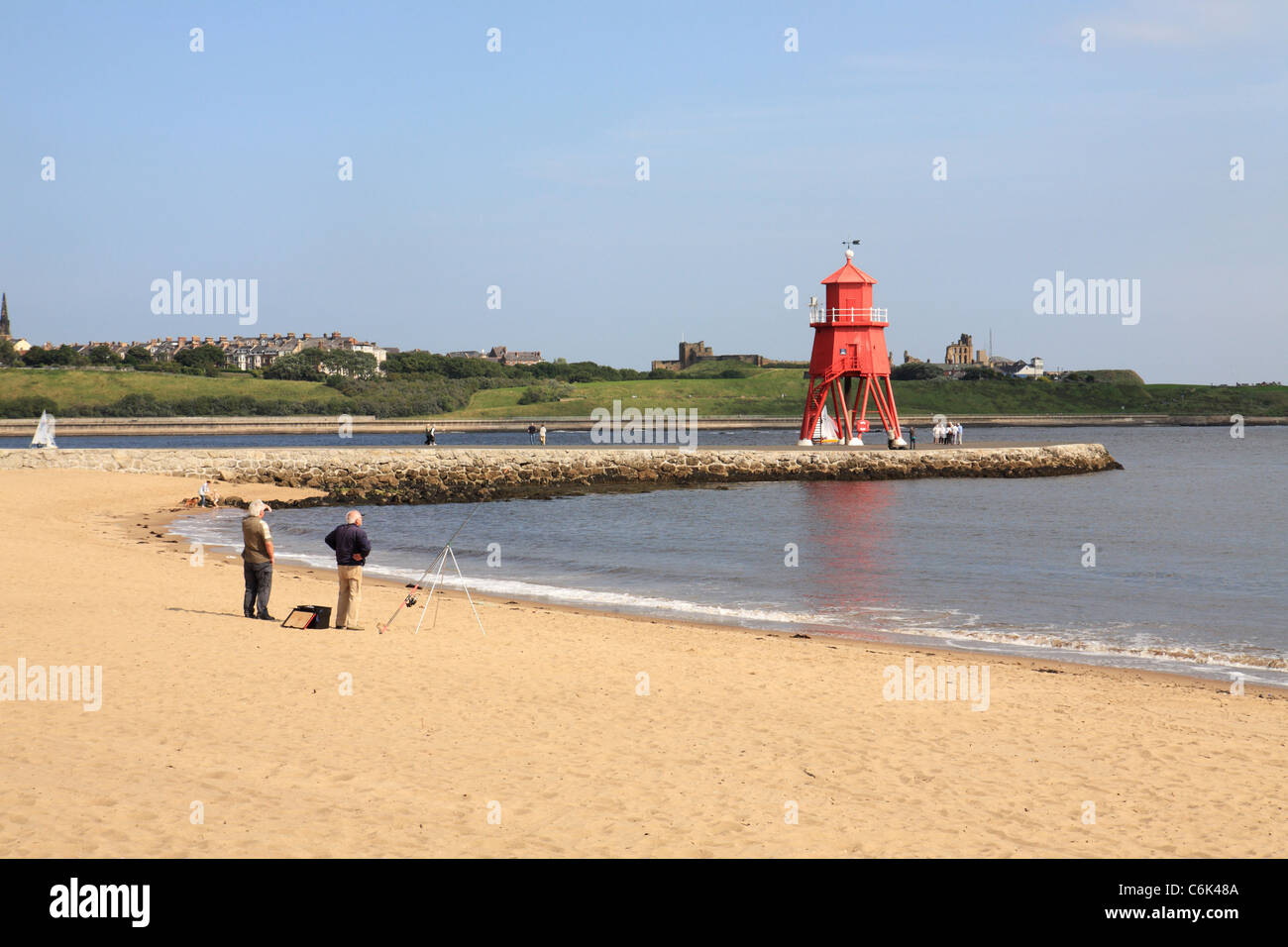 Two men fishing from Herd Sand or Littlehaven beach, Groyne lighthouse in background at South Shields, North East - Stock Image