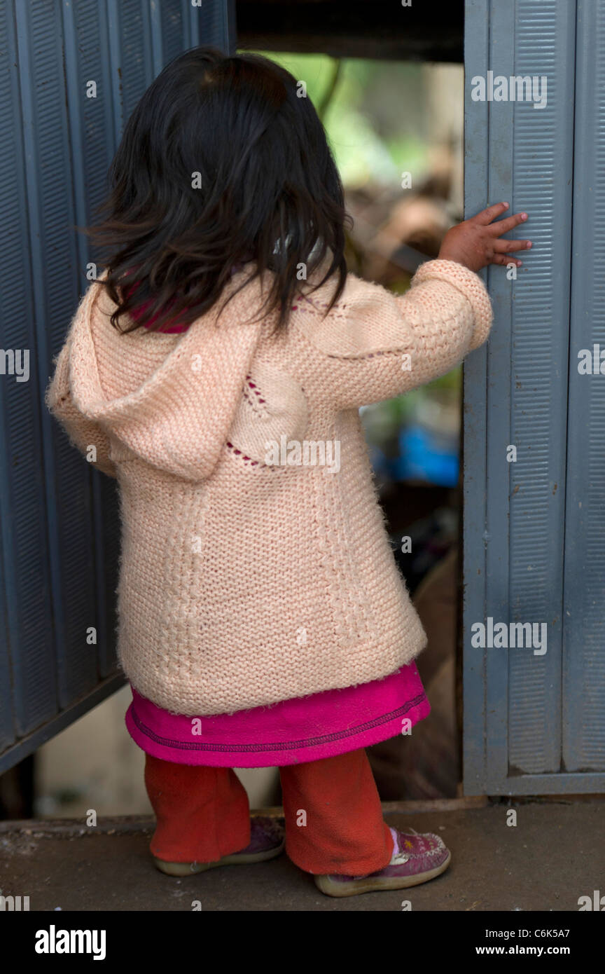 Small girl standing at a doorway, Sacred Valley, Cusco Region, Peru - Stock Image