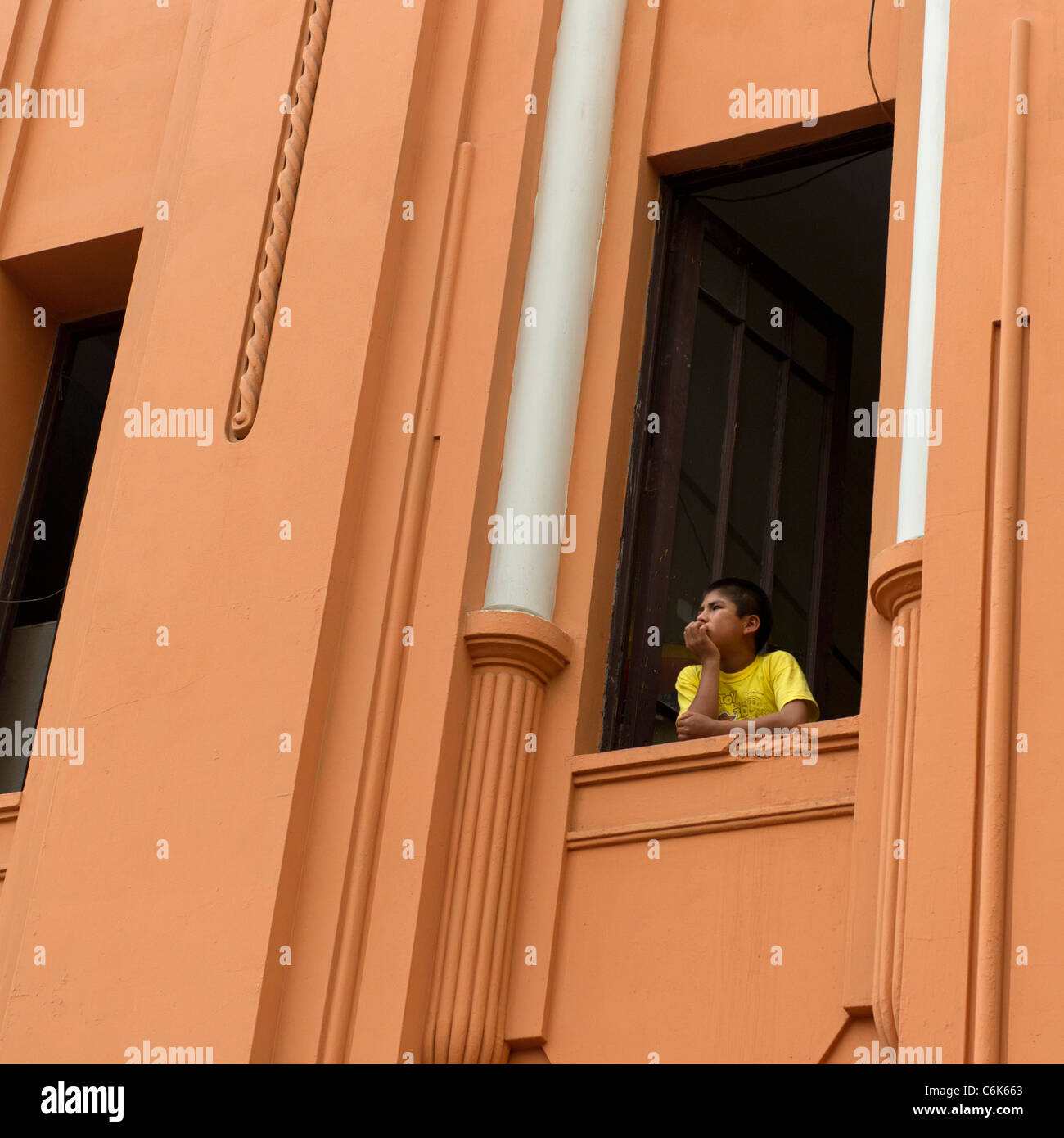 Boy looking through the window of a building in Historic Centre of Lima, Lima, Peru - Stock Image