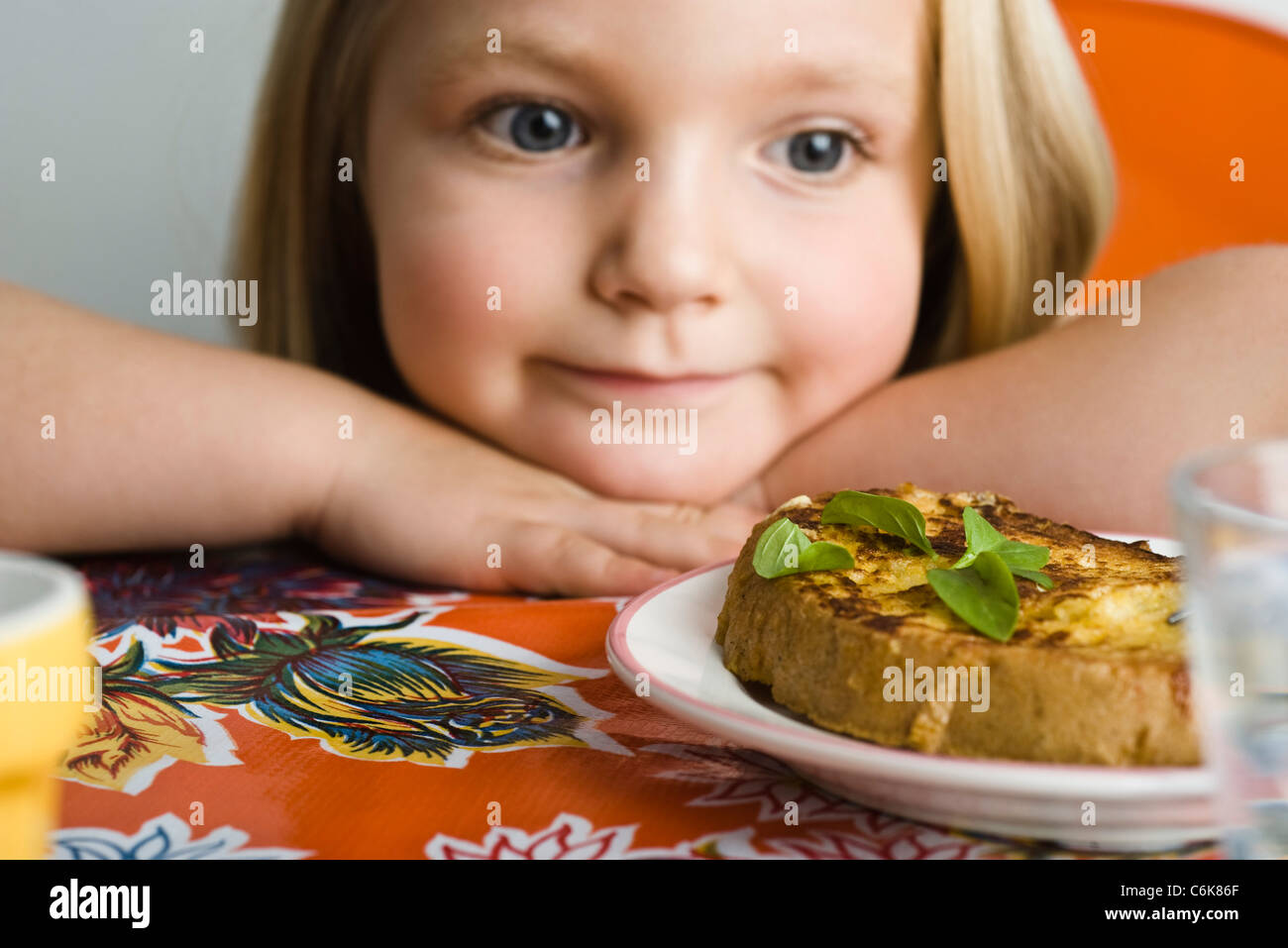 Little girl preparing to eat savory french toast - Stock Image