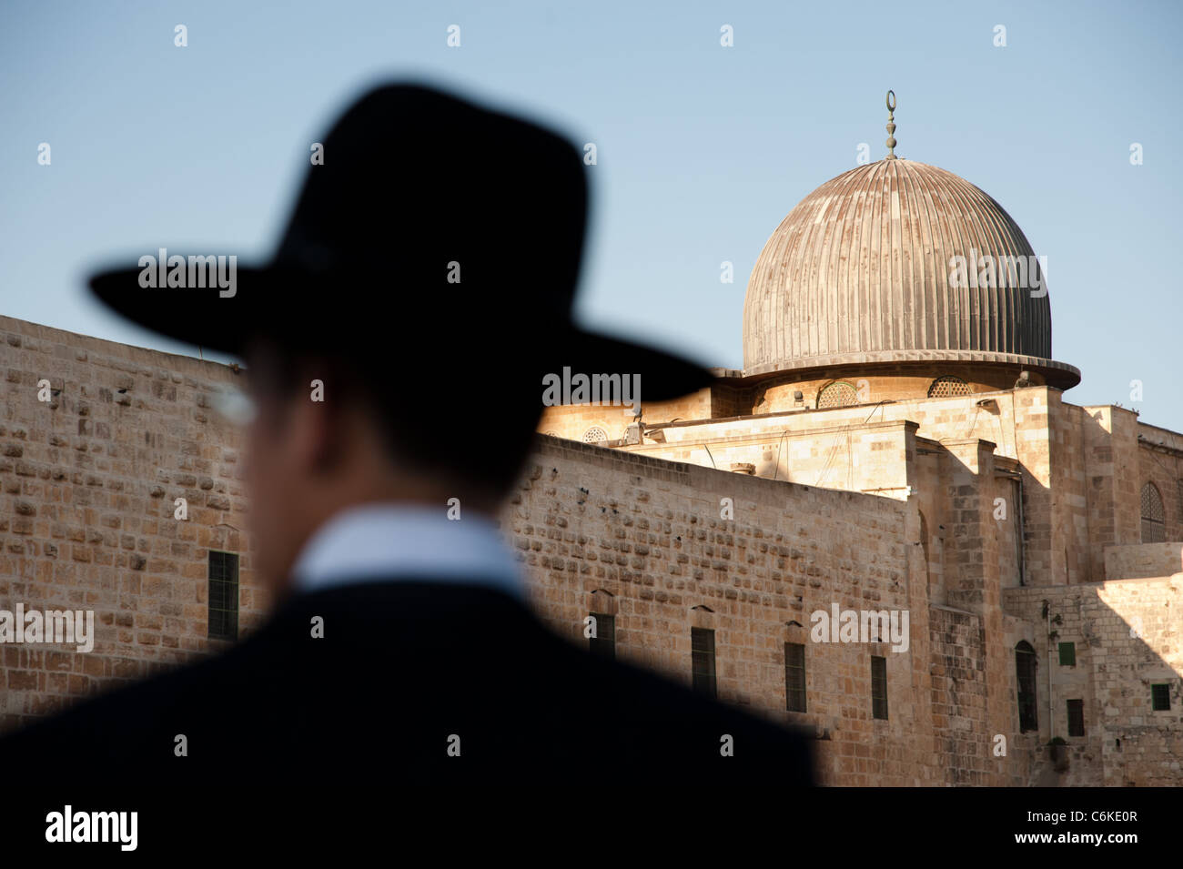 Ultra-orthodox Jews stand silhouetted against the dome of the Al-Aqsa Mosque in Jerusalem's Old City. - Stock Image