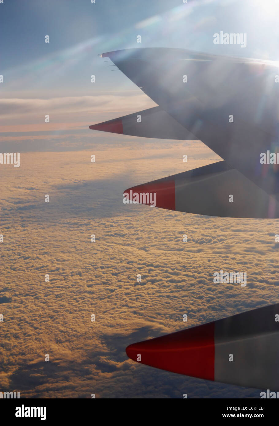 View from window seat of airplane wing over layer of cloud at sunset Stock Photo