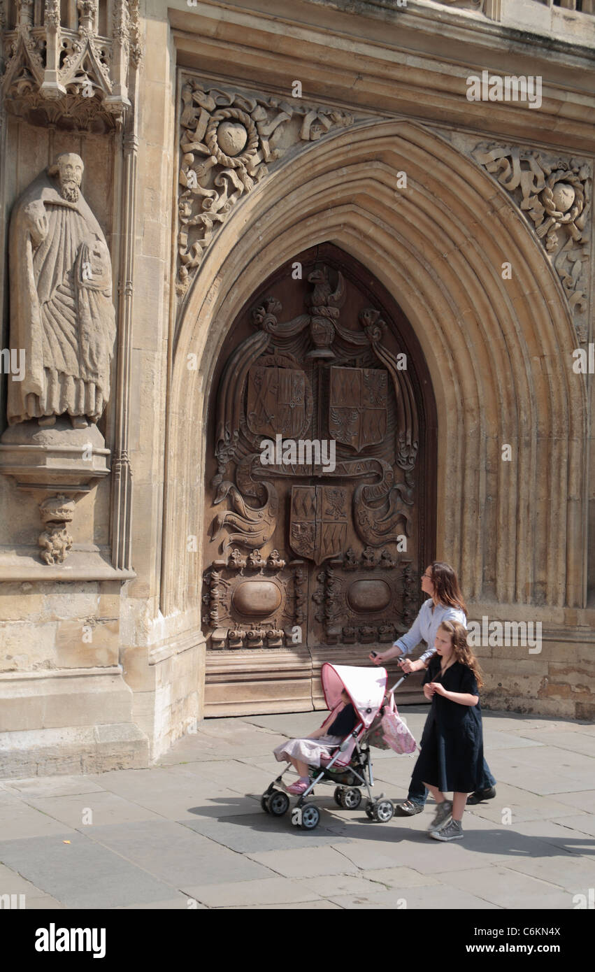 A lady with a child pushes her pushchair past the closed front door of Bath Abbey, Somerset, UK. Stock Photo