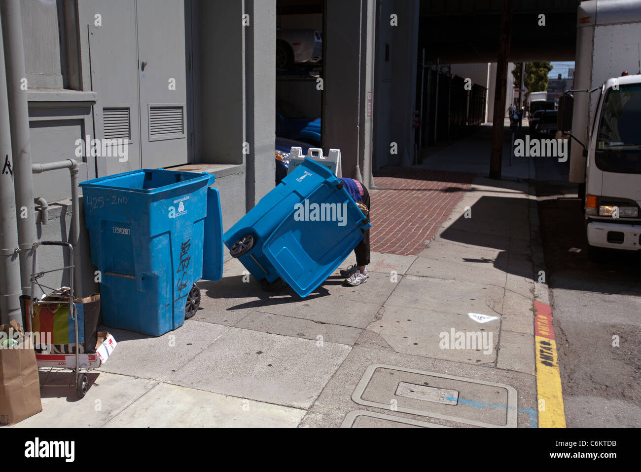 woman searching a garbage can in san francisco - Stock Image