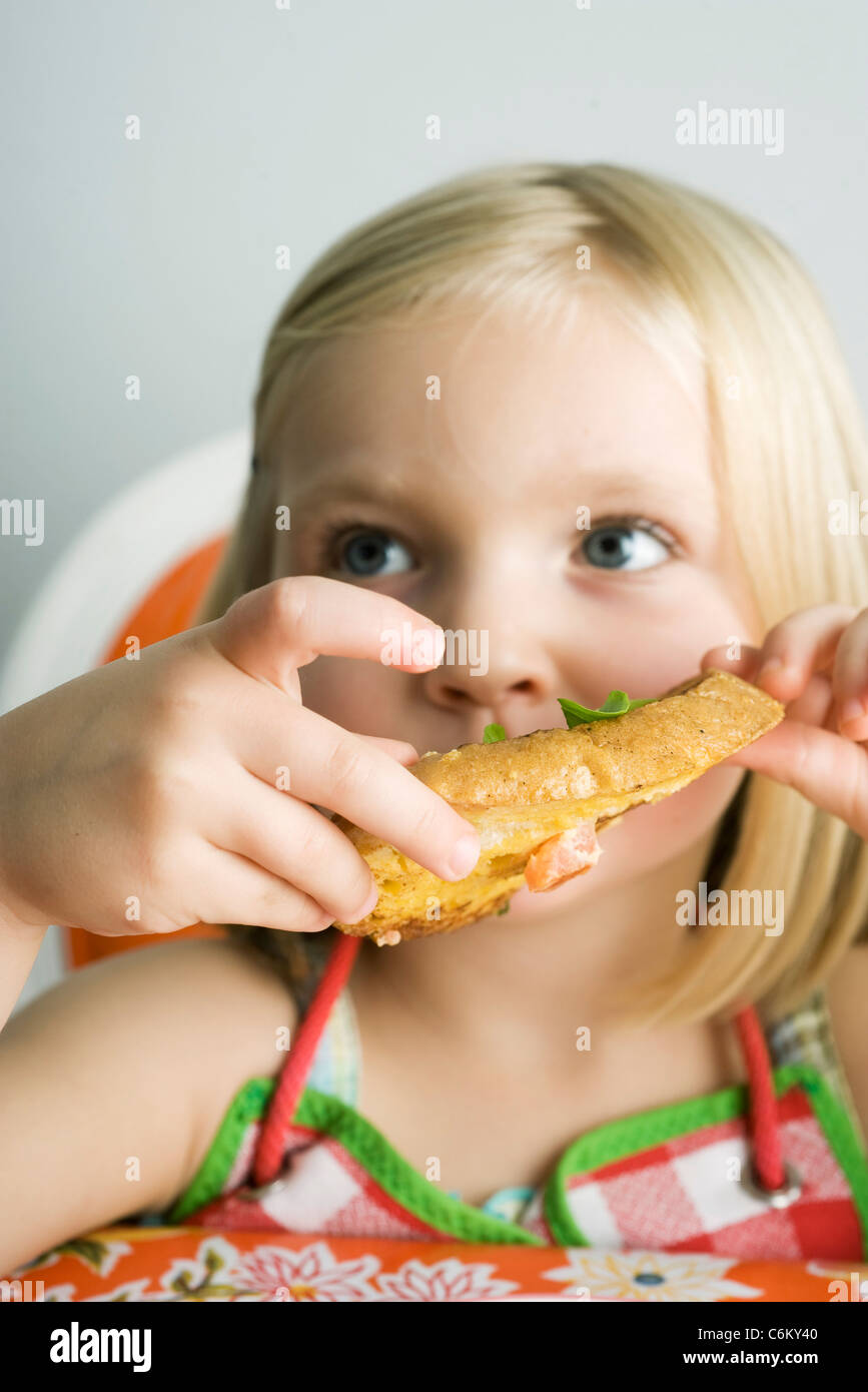 Little girl eating savory french toast - Stock Image
