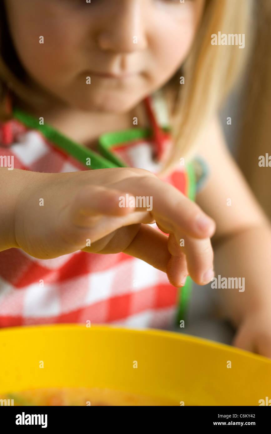 Little girl preparing food, cropped - Stock Image