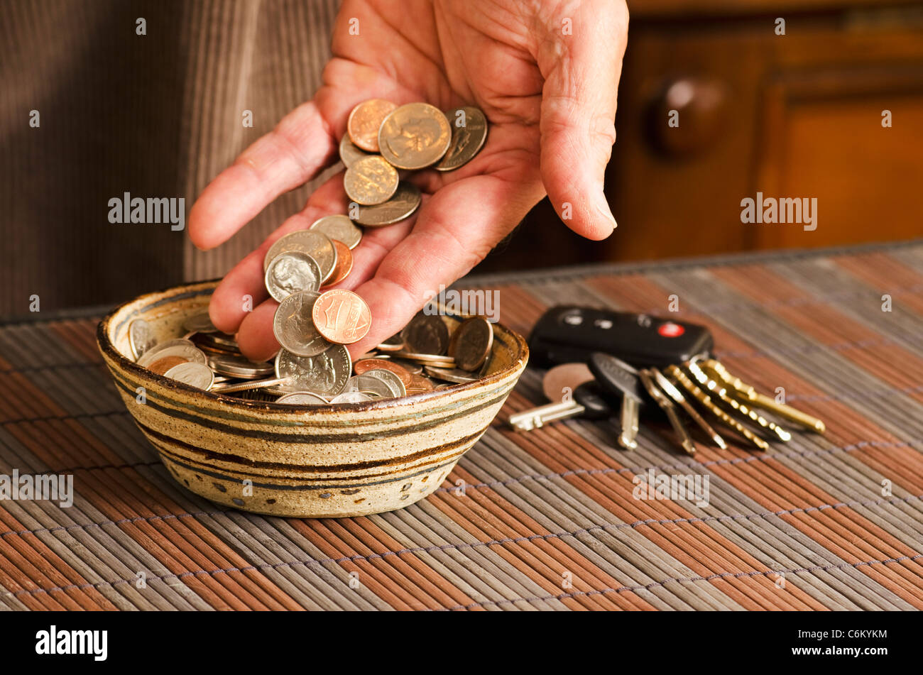 man placing daily pocket change in bowl - Stock Image