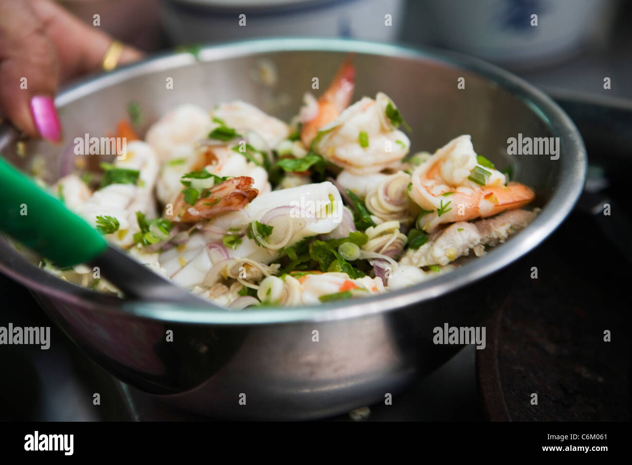 Preparing seafood salad with mint - Stock Image