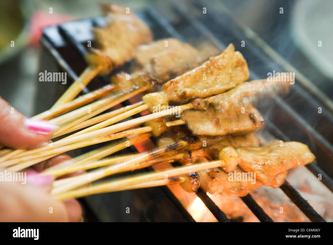 Grilling pork skewers - Stock Image