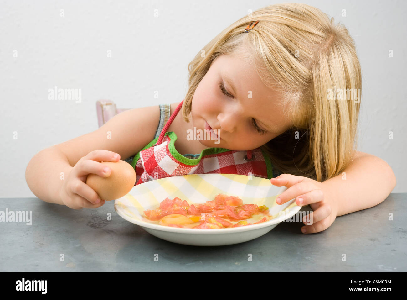 Little girl cracking egg - Stock Image