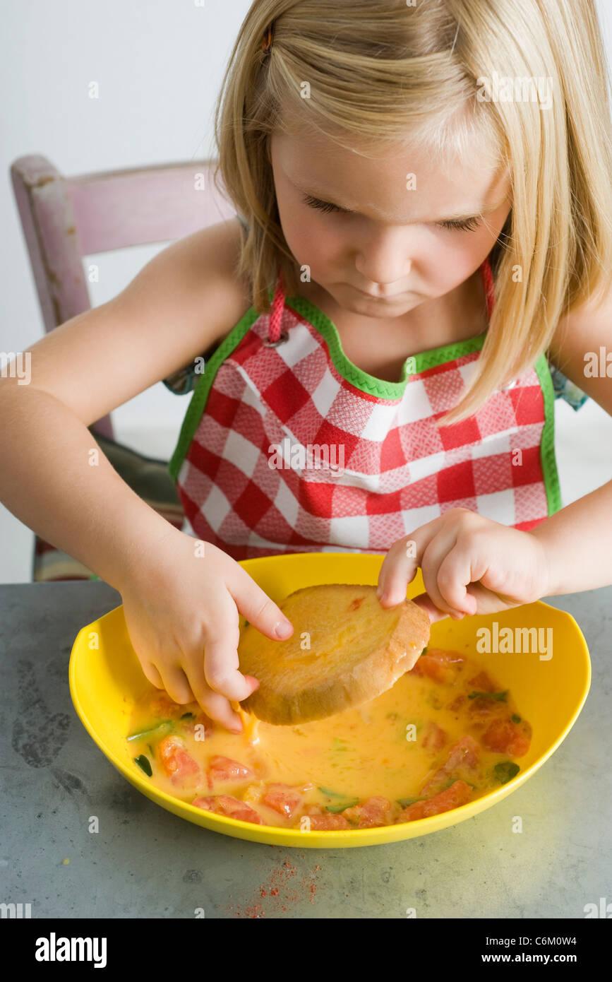 Little girl dipping bread in egg batter - Stock Image