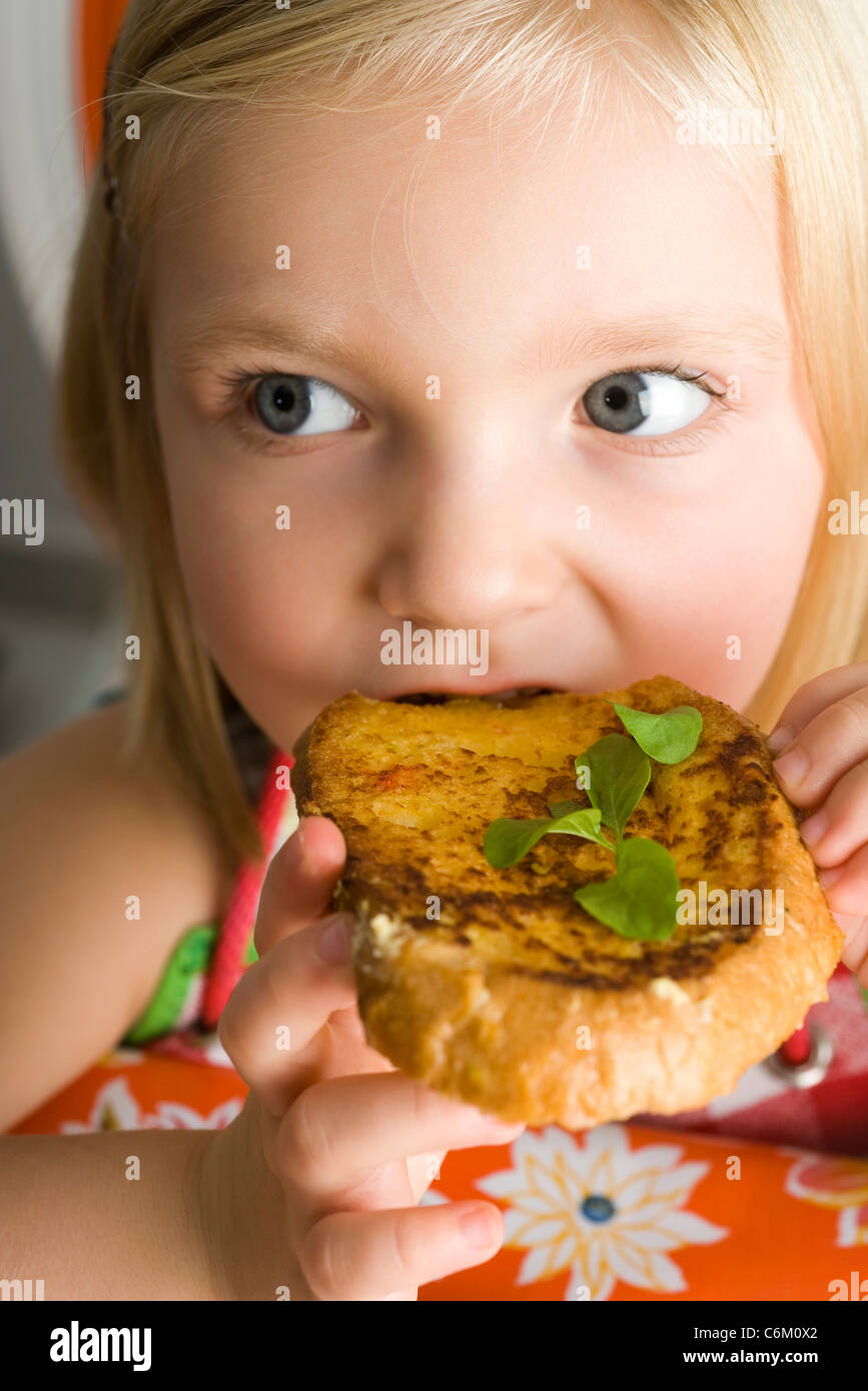 Little girl eating toasted bread Stock Photo