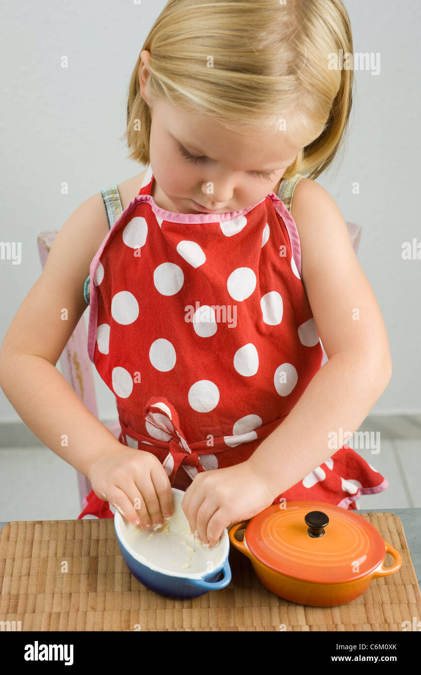 Little girl greasing small casserole dish Stock Photo
