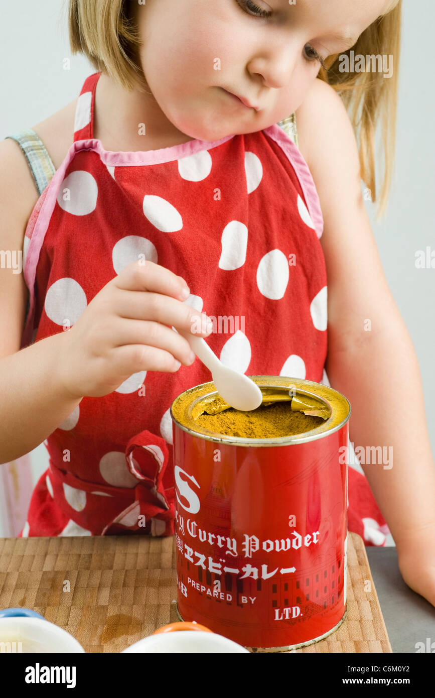 Little girl scooping curry powder from can - Stock Image