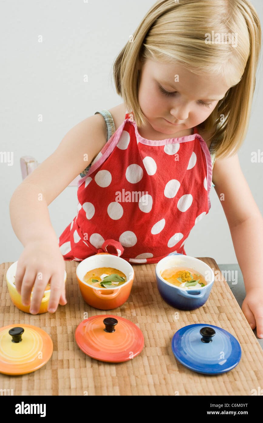 Little girl preparing baked eggs in small casserole dishes Stock Photo