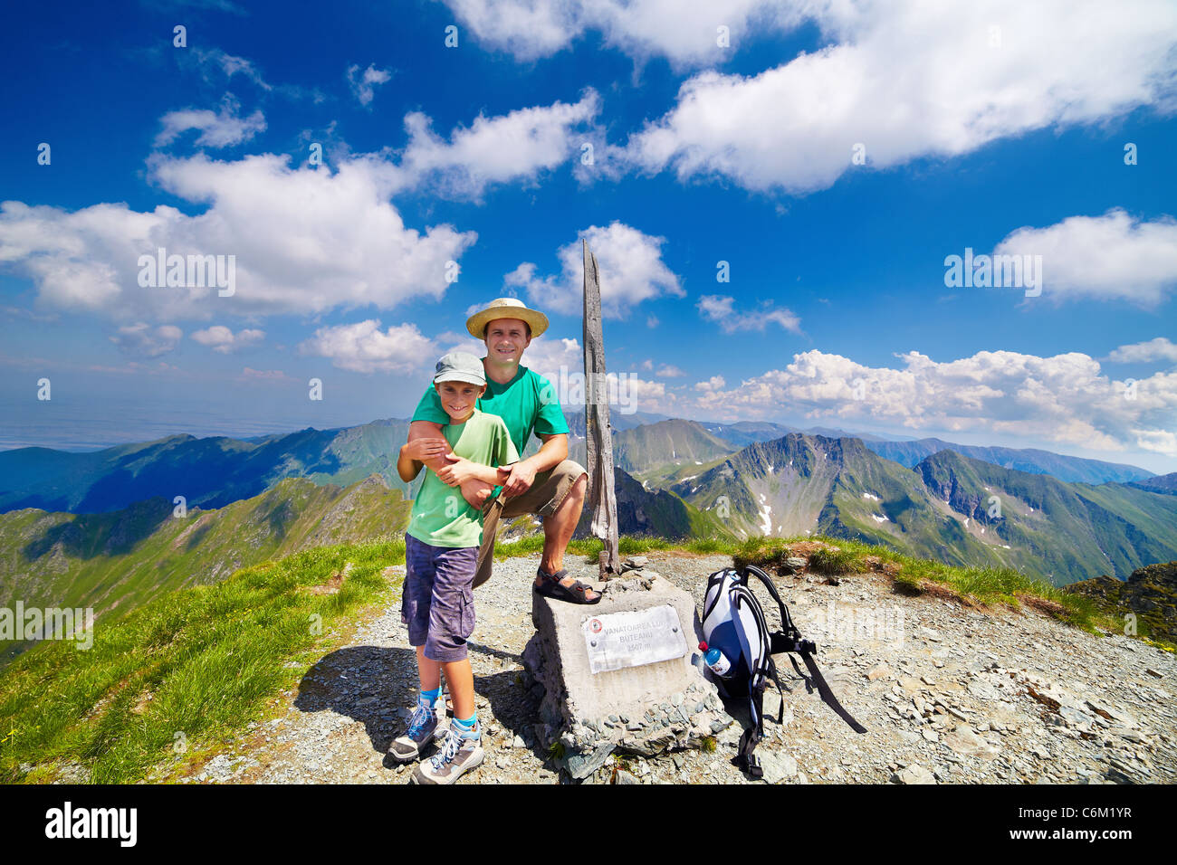 Happy father and son on the Buteanu peak in Romanian Carpathians, the inscriptions reads 'Peak Buteanu, 2507 - Stock Image