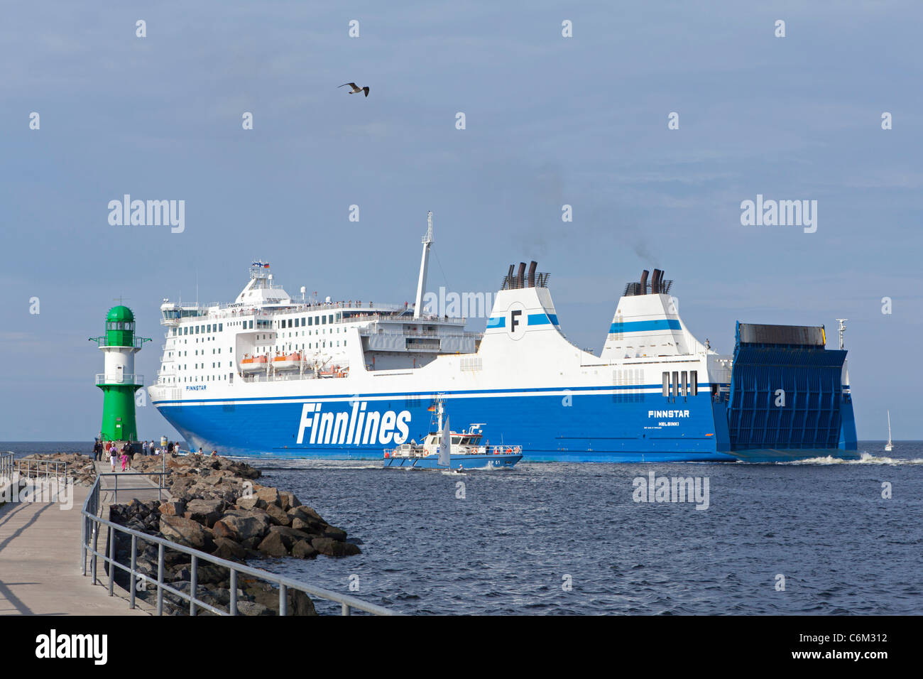 ferry passing the lighthouse into the Baltic Sea, Warnemuende, Rostock, Baltic Sea Coast, Mecklenburg-West Pomerania, - Stock Image