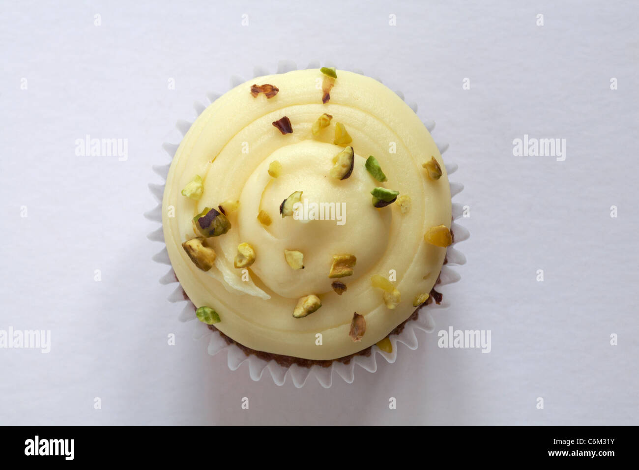 Looking down onto a carrot and walnut cupcake isolated on white background - from above - Stock Image
