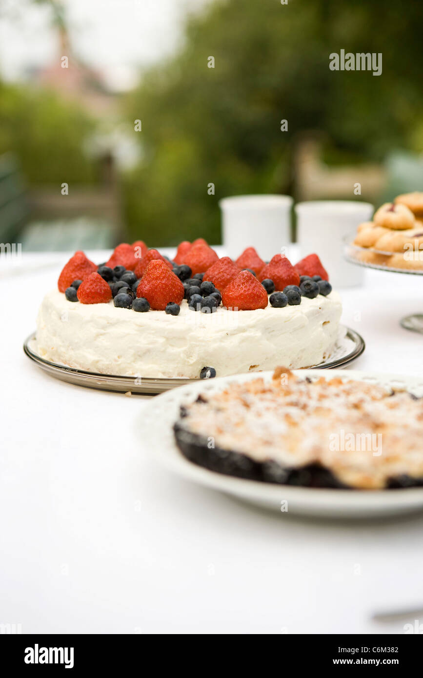 Strawberry blueberry cake and blueberry crumble on dessert table - Stock Image