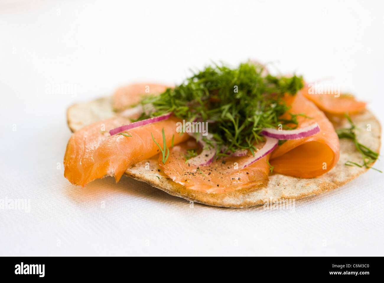 Crisp bread topped with smoked salmon and fresh dill - Stock Image