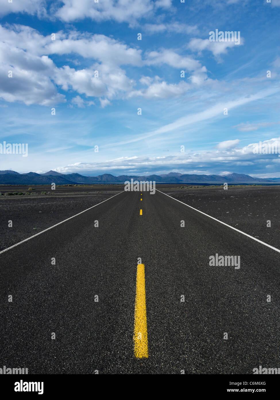 blacktop highway running through landscape of black sand - Stock Image