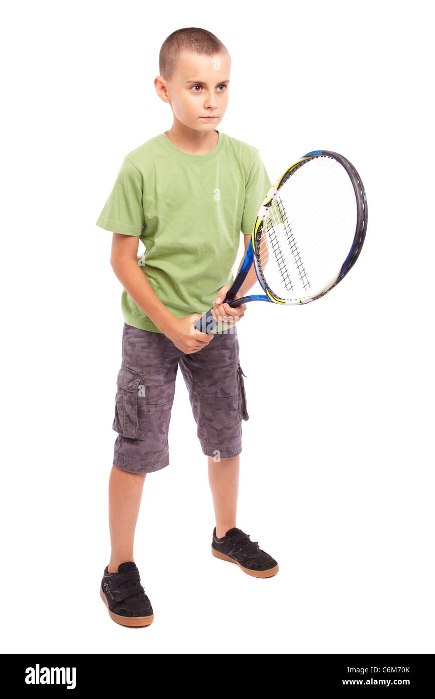Child playing training with a field tennis raquet, studio full length portrait - Stock Image